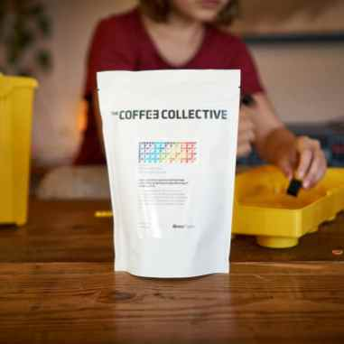 Coffee Collective coffee packaging with kid playing with legos in the background