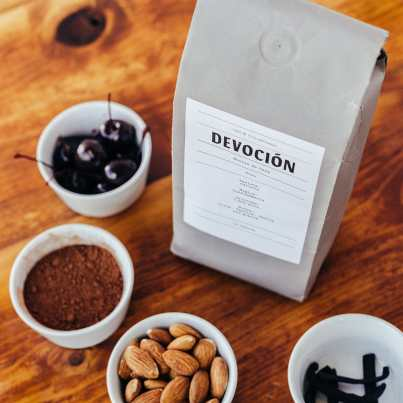 Devoción coffee bag with cups of cherries, vanilla bean, cocoa, and almonds