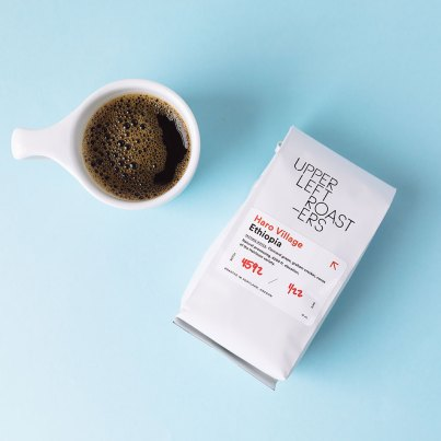 Upper Left Roasters coffee bag with cup of coffee on blue background