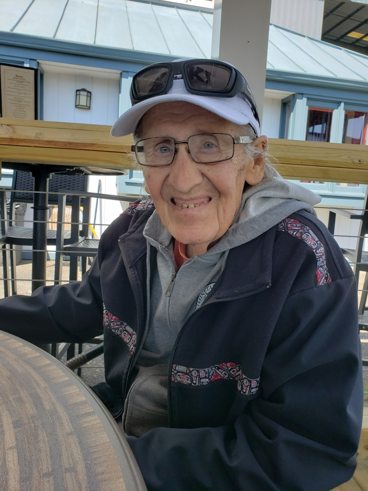 Man wearing glasses on his face and sunglasses on his baseball hat with a hoodie and a jacket. Hotel in the backgroun. He's sitting at a table smiling