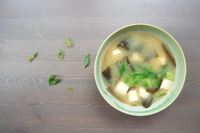 miso soup in bowl with wooden background and scallions