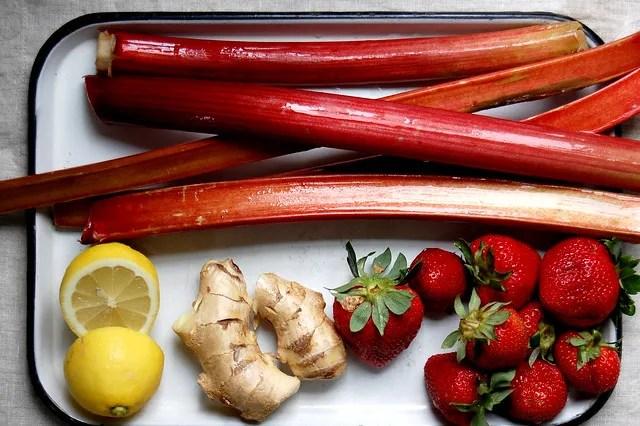 raw rhubarb, strawberries, lemon, and ginger on white tray