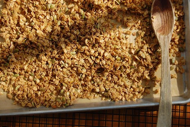 honey maple granola in sheet pan with wooden spoon