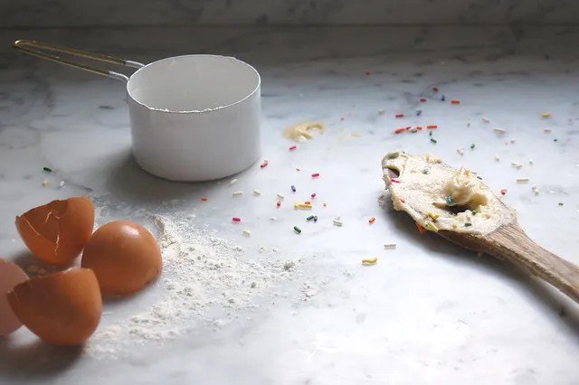 cake batter on wooden spoon with egg shells and cup