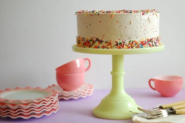 birthday sprinkle cake on yellow pedestal with pink cake plates and cups