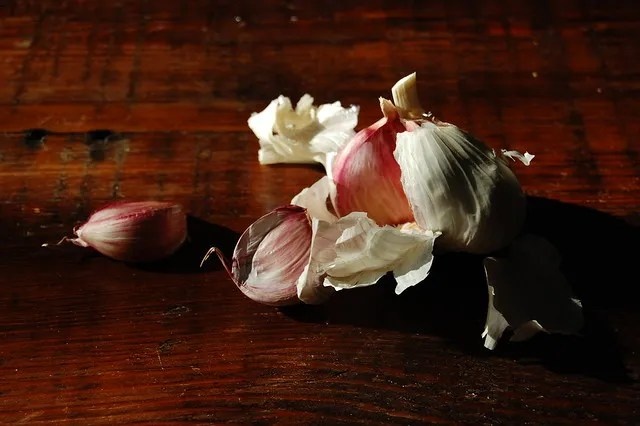 garlic on dark wood board