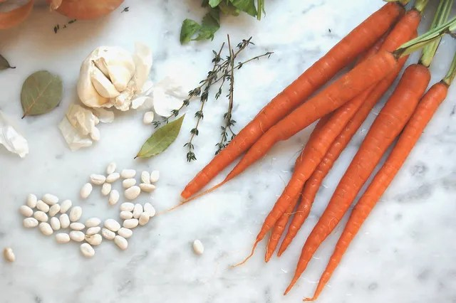 white bean soup pasta e fagioli ingredients carrots beans garlic herbs on marble