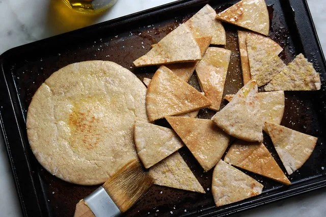 sliced and whole pita chips on baking sheet