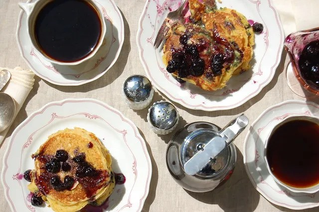 plates of blueberry pancakes with coffee and syrup