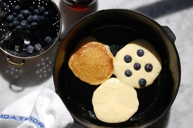 pancakes cooking in cast-iron skilled with blueberries