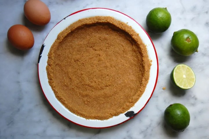 graham cracker crust with limes and egg on marble