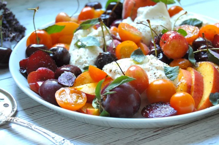 white platter of burrata and stone fruit caprese with basil peaches cherries caprese