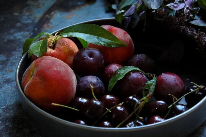 gray bowl of summer fruit peaches cherries plums