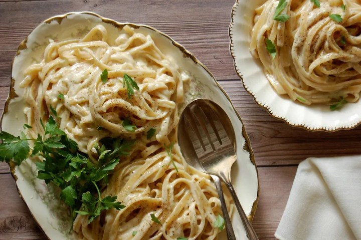 serving platter of fettuccini alfredo with parsley on wooden table