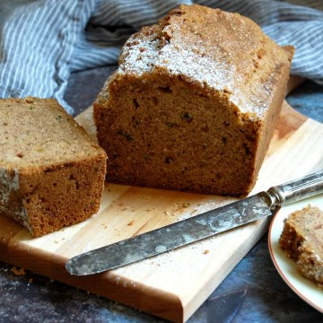 sliced zucchini bread with knife on wood board