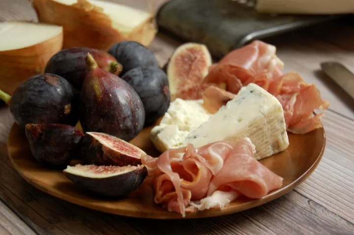 wooden platter of pizza ingredients goronzola figs prosciutto cheese