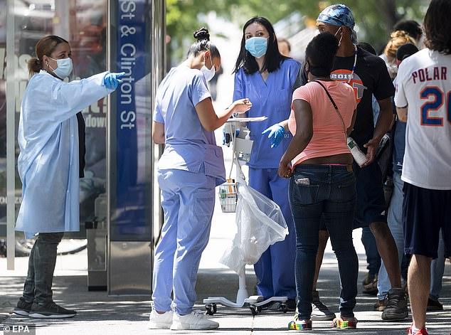 Le 21 juillet, des agents de santé enregistrent les patients dans un centre de dépistage du COVID-19 géré par la ville à New York