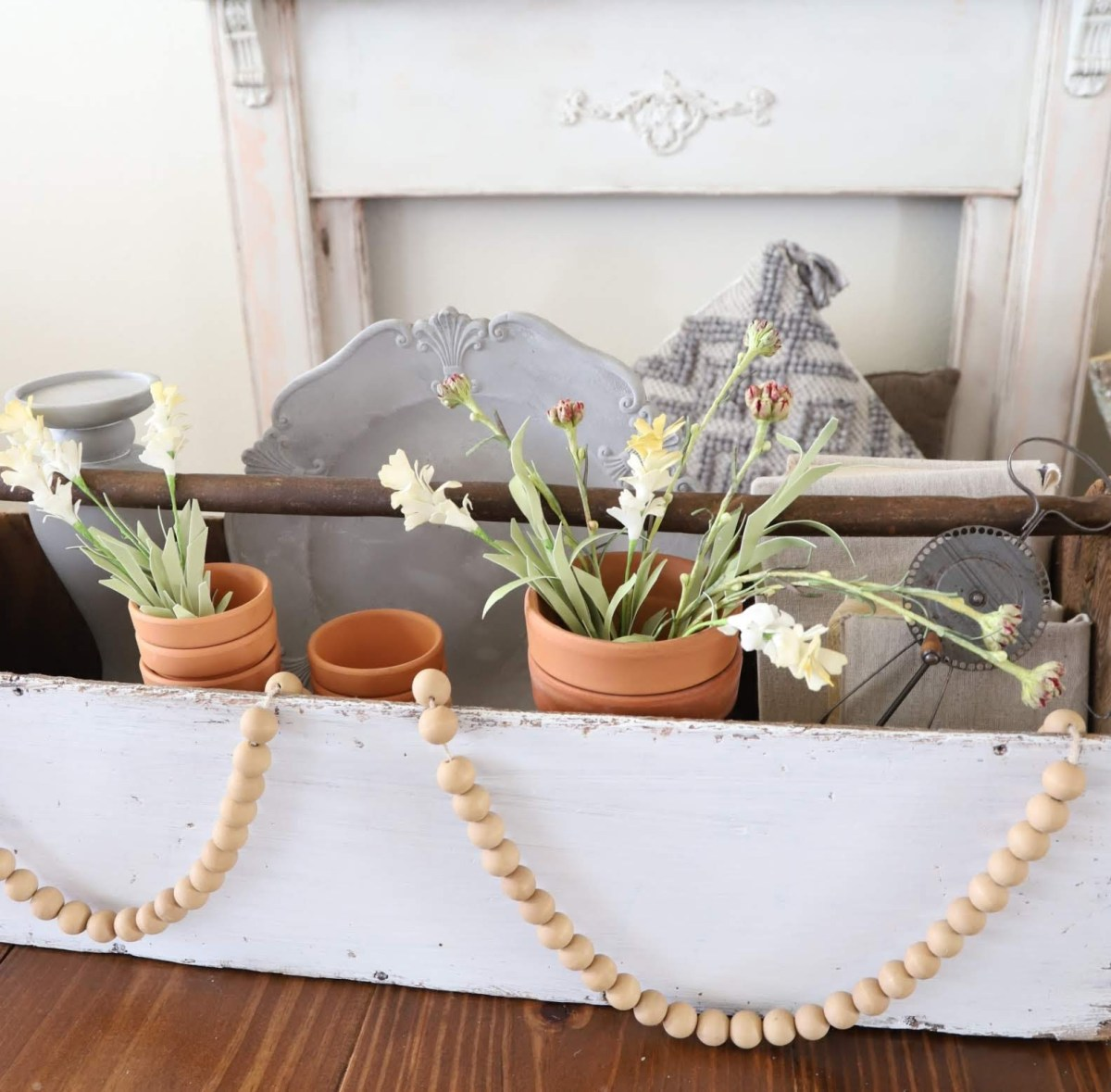 antique mantel, spring display in an old toolbox. terracotta pots