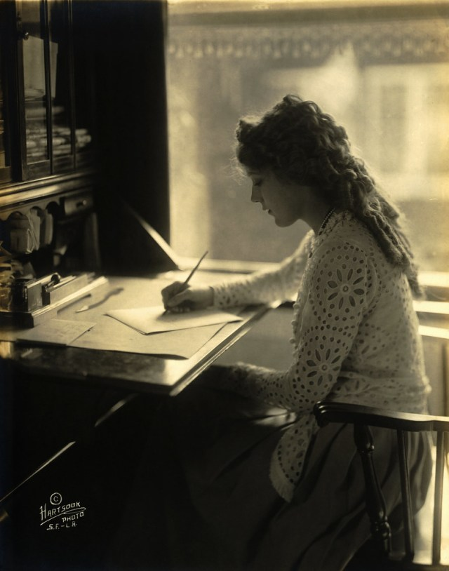 Actress Mary Pickford writing at a desk, by Hartsook Photo Studio, San Francisco & Los Angeles, California, 23 March 1918.
