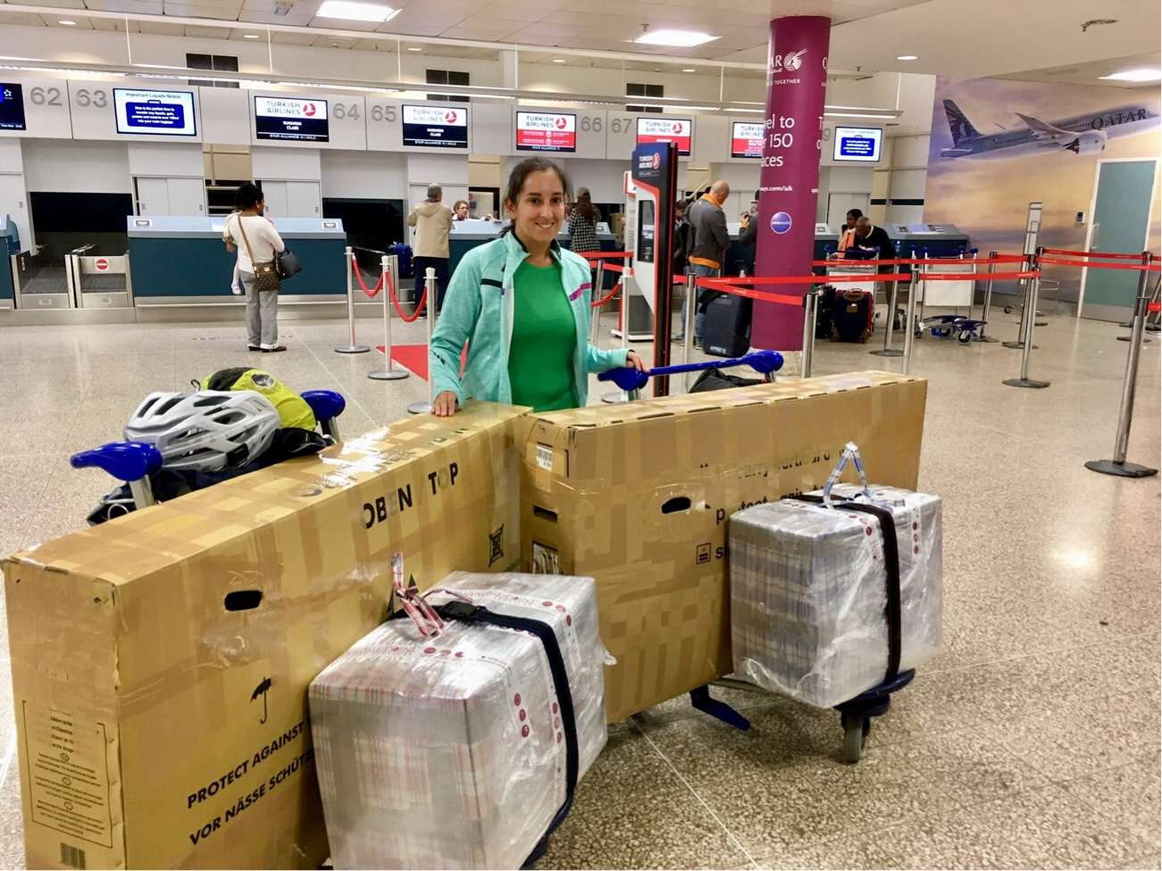 Steph stood with bike boxes and bags in Birmingham airport ready for our flight to Argentina