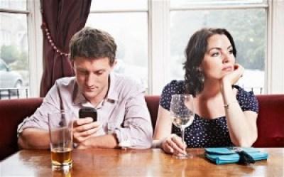 Hombre usando su móvil mientras su novia espera aburrida