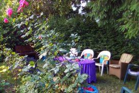Tisch hinter Rosenbusch