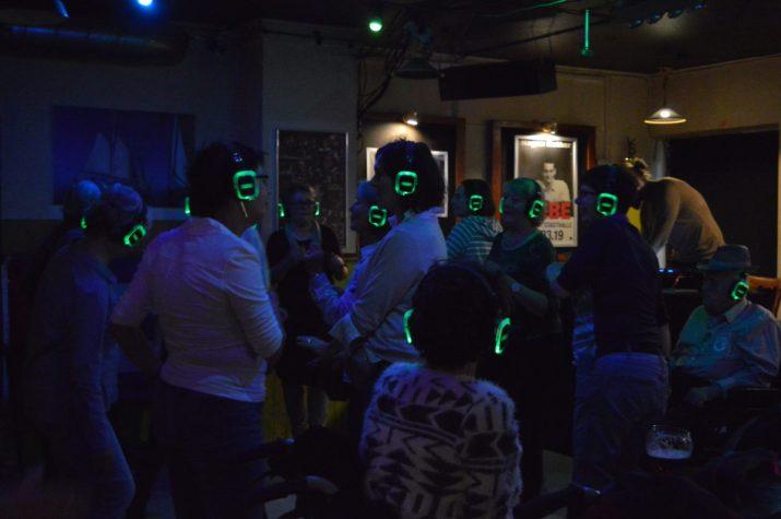 Menschen mit leuchtenden Kopfhörern tanzen