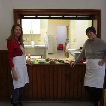Zwei Ehrenamtlerinnen vor dem Frühstücksbuffet.