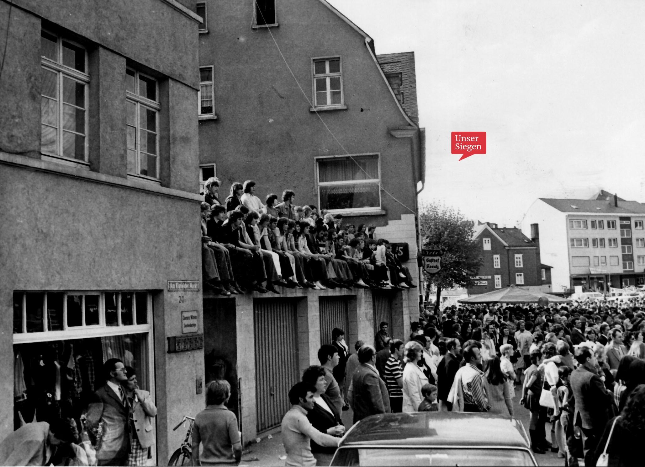 Schwarz-Weiß-Bild aus dem Jahr 1972. Viele Menschen stehen auf dem Geisweider Marktplatz. Es ist sehr voll. Einige Zuschauer sitzen auf einem Garagendach.