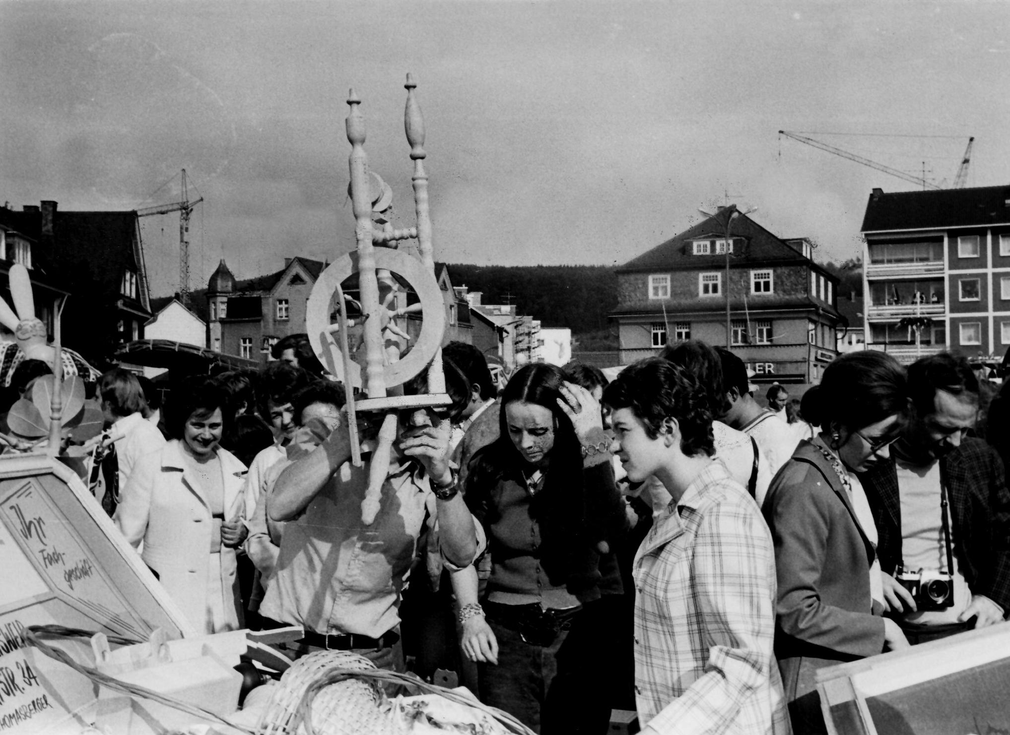 Scharz-Weiß-Bild aus dem Jahr 1972. Mehrere Menschen stehen vor einem Stand auf dem Flohmarkt in Geisweid. Eine Dame hält ein Spinnrad in die Höhe