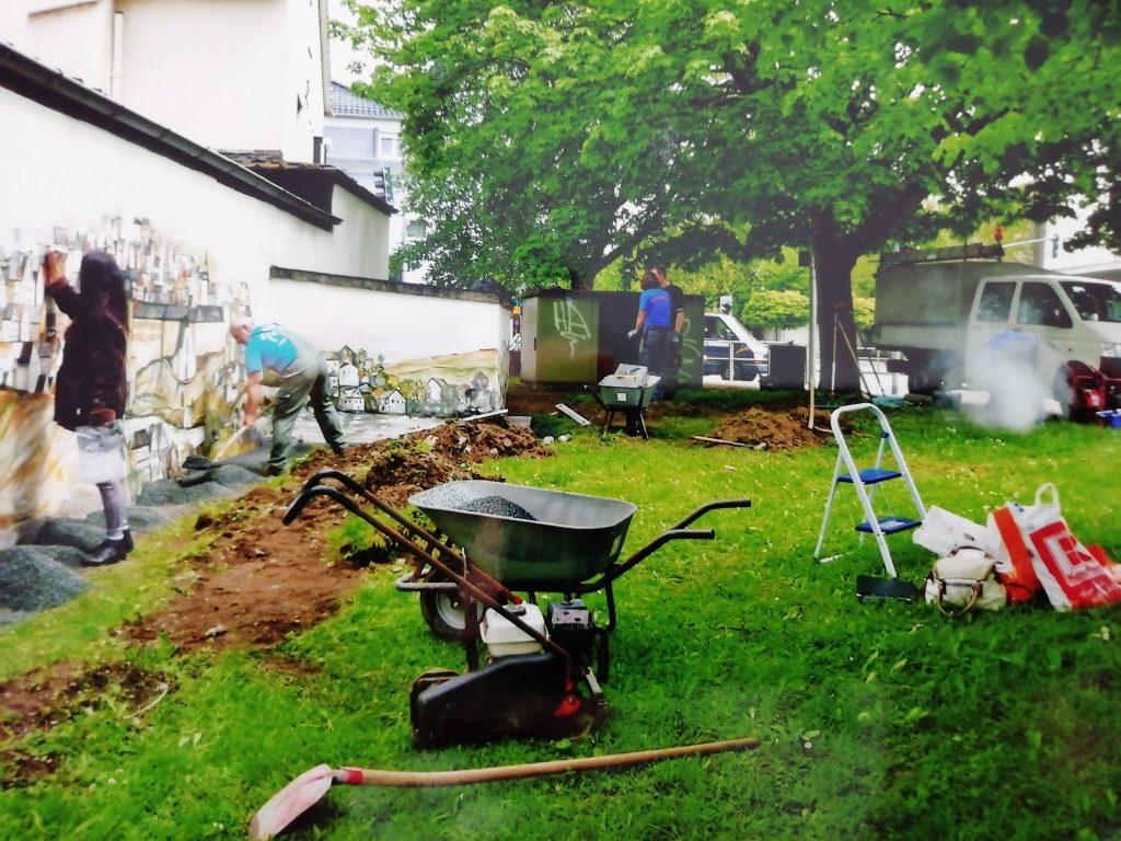 """Renovierungs- und Malerarbeiten an alter Mauer am Fuße des Fischbacherbergs. Tzveta Grebe malt für das Projekt """"Siegen sind wir"""" eine Ansicht der Siegener Altstadt auf die Wand."""