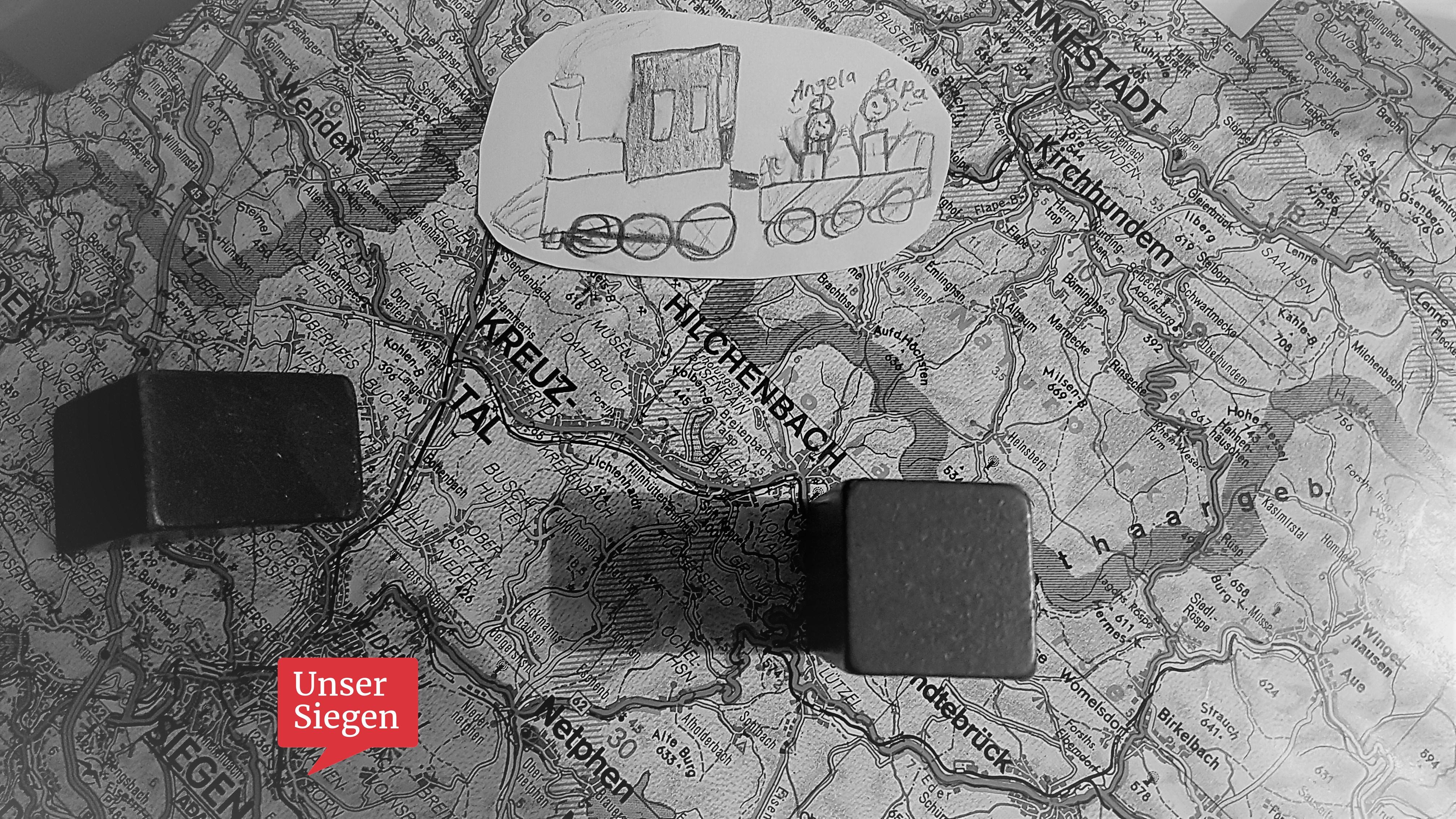 Auf einer Landkarte des Siegerlandes liegt eine gemalte Skizze. Das Bild zeigt eine gezeichnete Lokomotive mit einem Anhänger in dem ein Kind und sein Vater zu sehen sind.
