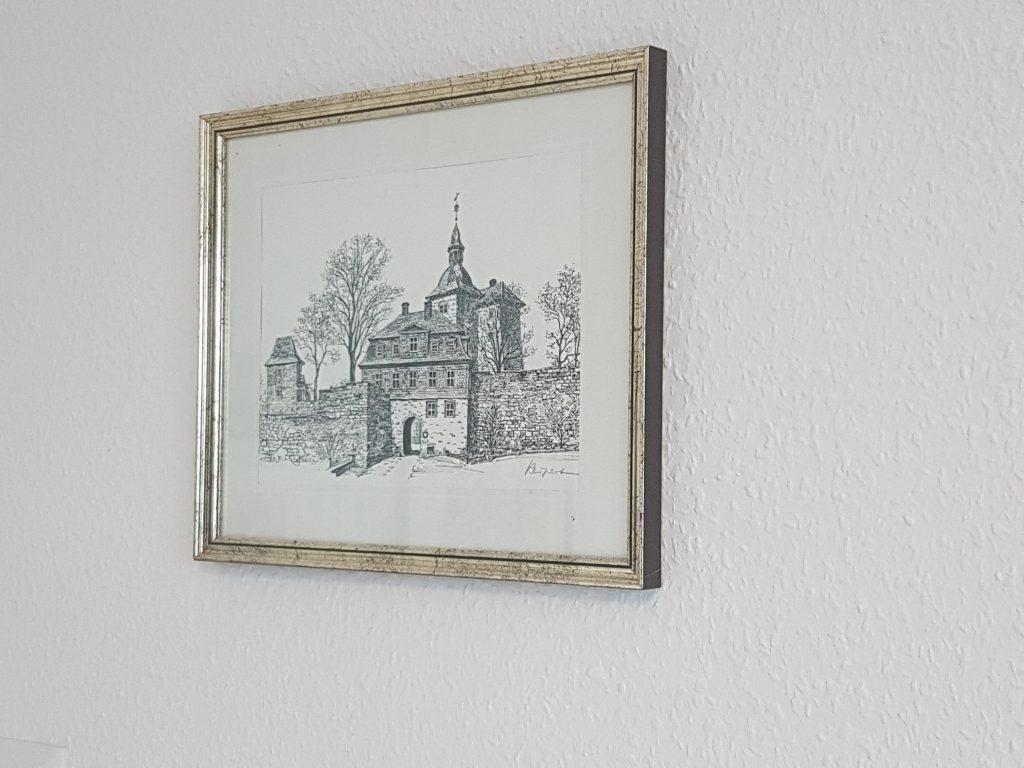 Ein goldener Bilderrahmen an einer Zimmerwand. Eingerahmt ist eine Schwarz-Weiß-Skizze vom Oberen Schloss in Siegen