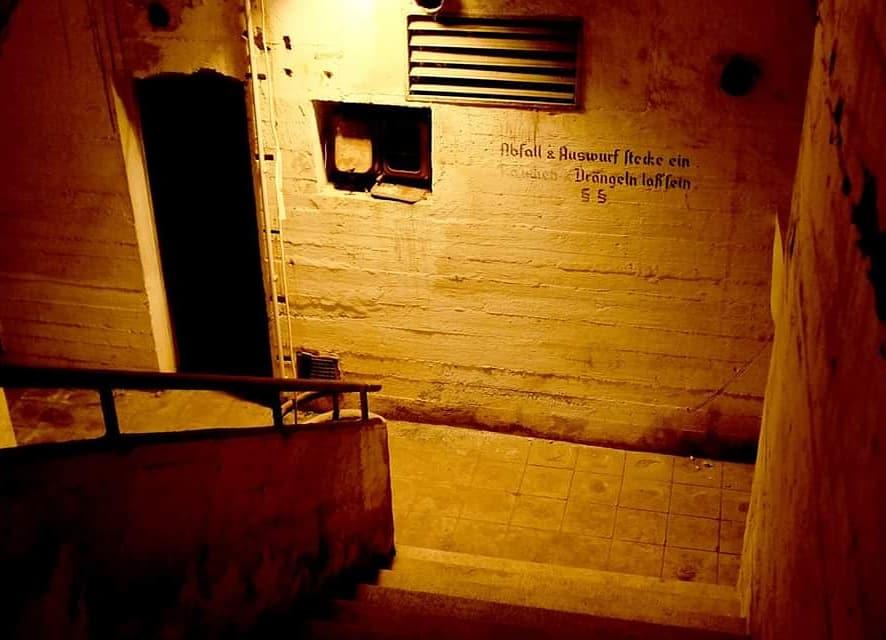 Innenansicht des Bunkers an der Burgstraße. Gedämpftes Licht. An der Wand steht aus Kriegszeiten geschrieben: Abfall und Auswurf stecke ein. Drängeln lassen