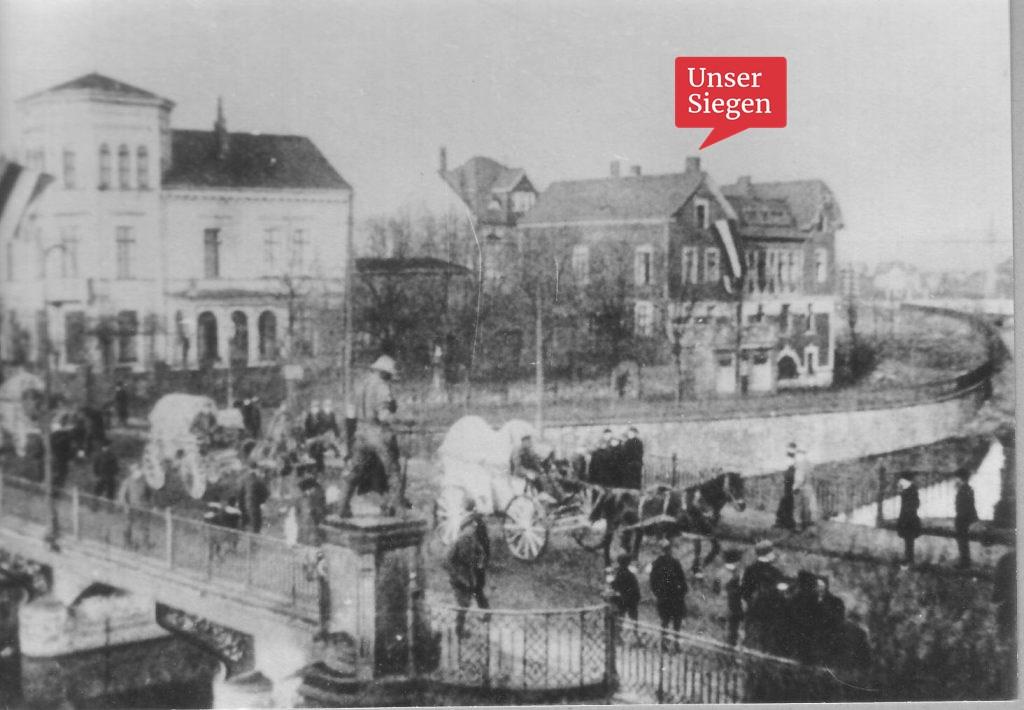Ein historisches Foto. Kutschen fahren über die Siegbrücke