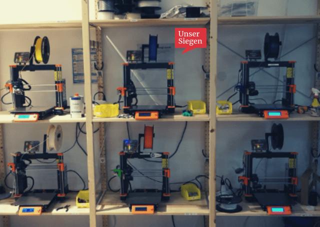 Die 3D-Drucker im FabLab der Universität Siegen. Ein einfaches Holzregal mit mehreren 3D-Druckern samt Material. Mit freundlicher Genehmigung von Lisa Neumann, FabLab Siegen.