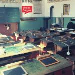 Ein Klassenraum, wie er in den 1930er/40er Jahren ausgesehen haben mag. Mehrere Schulbänke mit Schiefertafeln, ein alter Holzofen sowie Sütterlinschrift auf der Tafel. Foto: Nuffer auf Pixabay.com