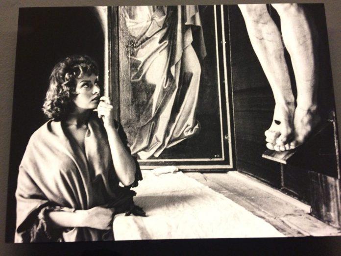 <em>Sophia Loren frente al crucifijo de Benvenuto Cellini durante el rodaje de 'Orgullo y Pasion' en el Monasterio de El Escorial. 1956. Getty Images. (Foto tomada en la exposición)</em>