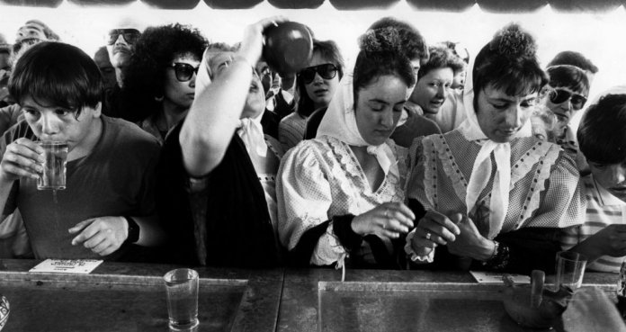 Unas jóvenes vestidas de chulapas, en el mostrador donde se reparte el agua en la milagrosa fuente del Santo el 15 de mayo de 1986. LUIS MAGÁN para El País.