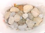 Der zweite Eimer wird befüllt: oben drauf kommt eine Plastiktüte und Steine zum beschweren.