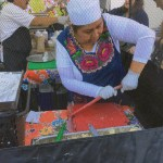 Woman pressing a tortilla at the Los Altos Farmers Market.