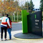 A couple taking a selfie next to the 1 Infinite Loop sign, Cupertino.