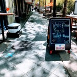 Sign in front of a bar in Mountain View offering white flour, yeast and toilet paper. Plus a delivery robot.