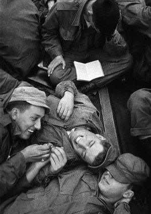 © Harold Feinstein, Soldiers lying on the deck of a crowded US military troopship to Korea pass the time talking and laughing while another reads, Unspecified location, 1952, © Harold Feinstein