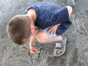 Issac drawing in the dirt in the shade at the playground--it was too hot to be on the equipment.
