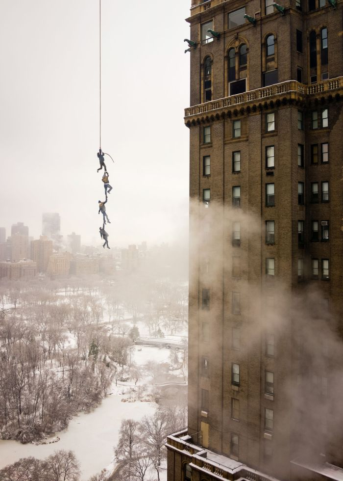 """A composite photo. The main image was shot from the 26th floor of a building in NYC. Then for the rest, I had four of my friends lie down in the snow and posed them as if they were dangling from a string. I photographed them from directly above so the perspectives would match and then carefully stitched the two images together in Photoshop."""