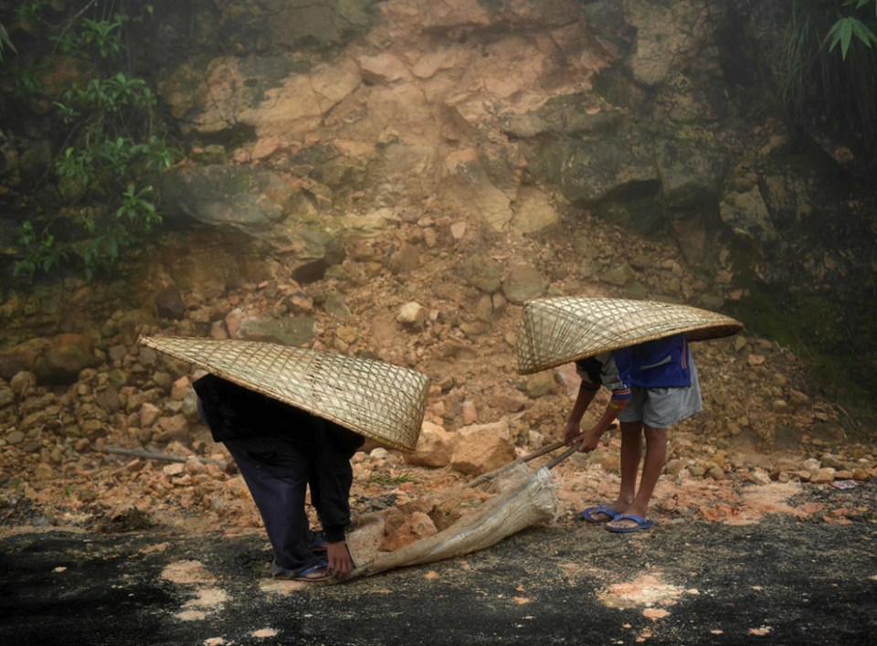 Laborers wearing knups clear rockfall after a night of heavy rain in Mawsynram. Major repair works are impossible through the monsoon rains but these men are tasked with keeping the roads passable until October when the rainy season ends and the contractors' heavy machinery can be brought in. They earn $2.60 per day. (© Amos Chapple)
