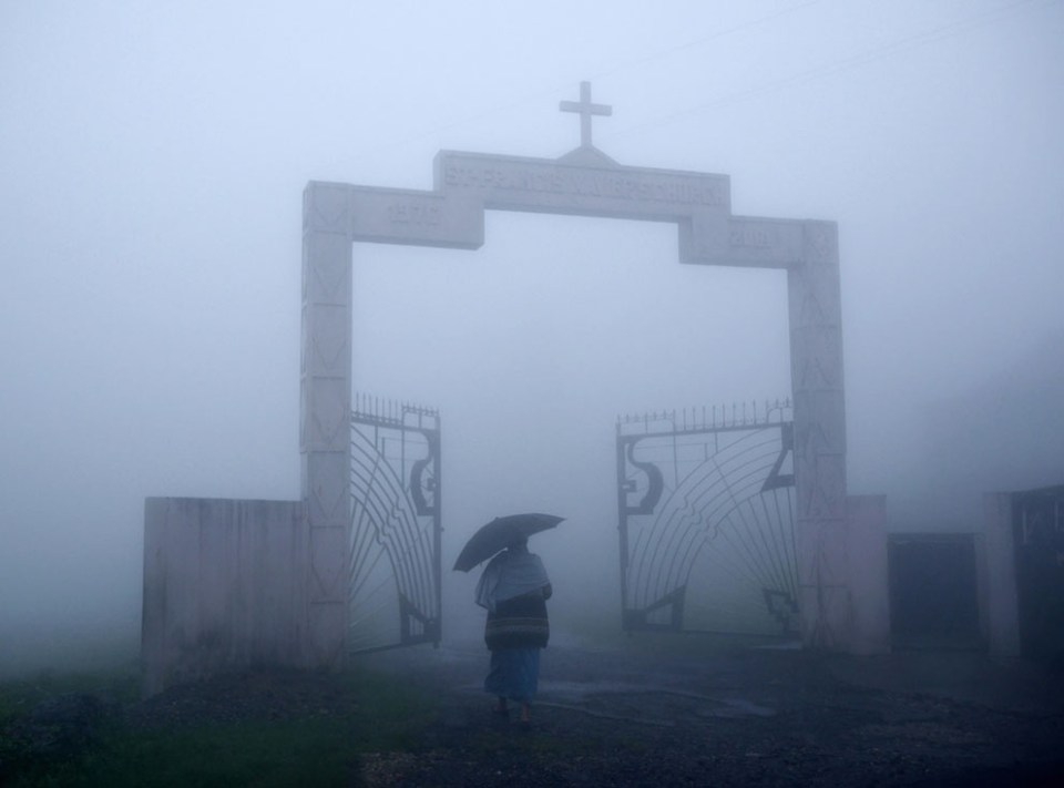 An elderly Khasi woman is the first arrival to Sunday mass in Mawsynram's Catholic church. Around 70% of Khasi are Christian, largely due to the Reverend Thomas Jones who, in 1841 clambered up into the hills from the plains of Bangladesh and established the region's first church in the neighboring town of Cherrapunji. (© Amos Chapple)