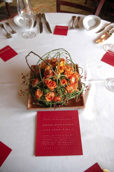 Table flowers with orange ranunculus and vines