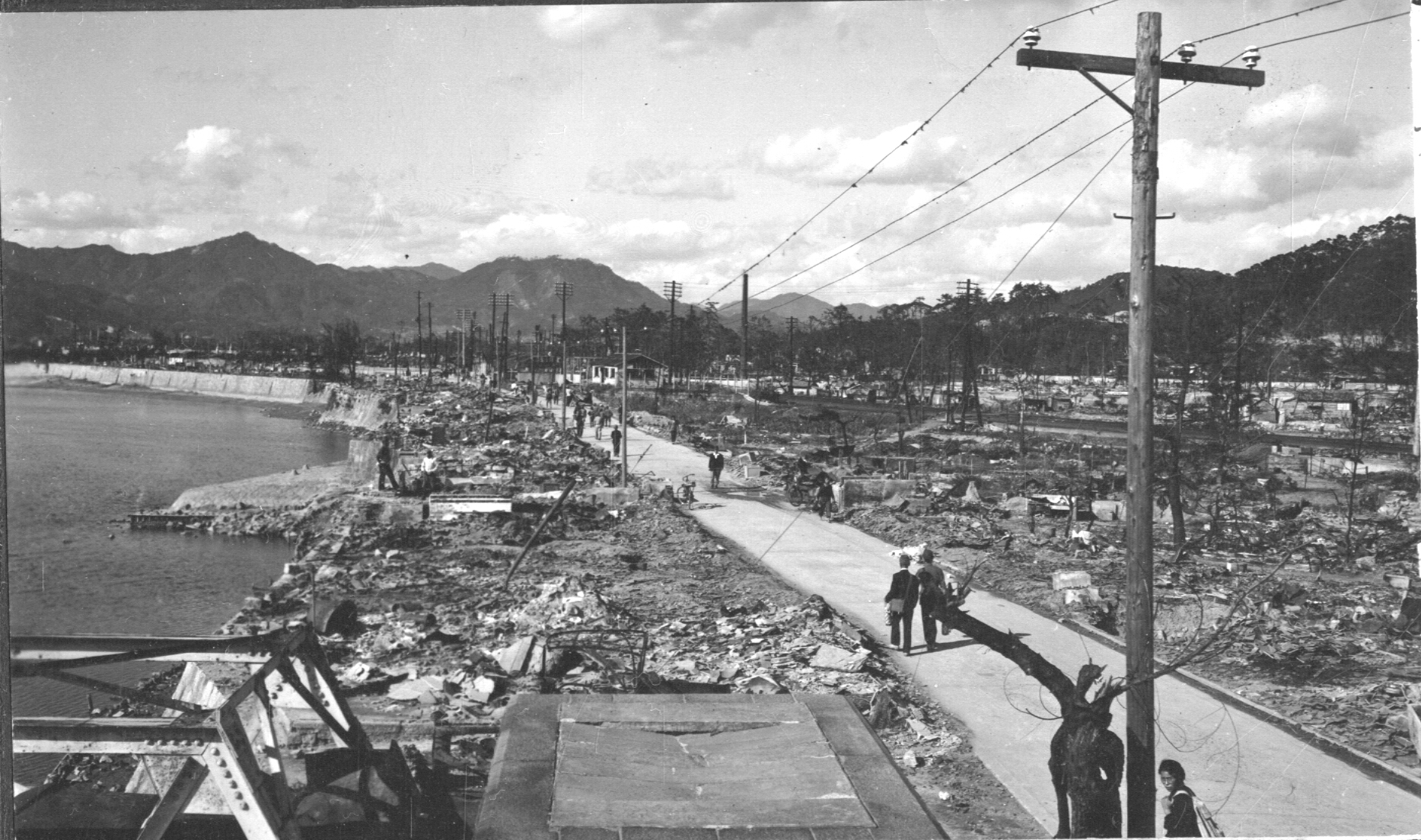 Photograph of Hiroshima after atomic bomb. People walk along a path. A stream or river is to the left of the frame. Power lines are intact.